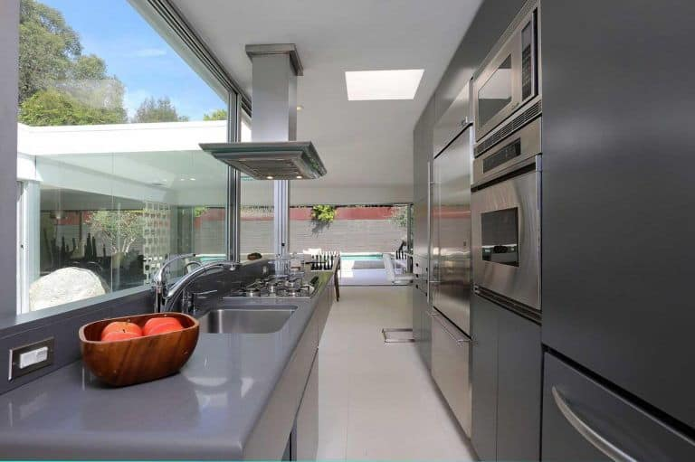 Modern kitchen showcases stainless steel appliances and gray cabinetry matching with the countertop. It includes a skylight and panoramic windows overlooking the sparkling swimming pool.