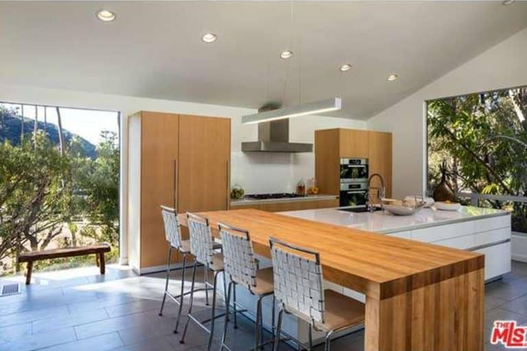 Woven counter chairs sit at a wooden eating counter that's attached to a white central island. This kitchen has brick tiled flooring and full-height windows overlooking the outdoor scenery.