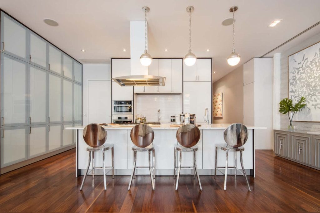 This kitchen offers floor to ceiling cabinets and a marble top island lighted by glass globe pendants. It is complemented by a sleek range hood and chrome round back stools over the rich hardwood flooring.