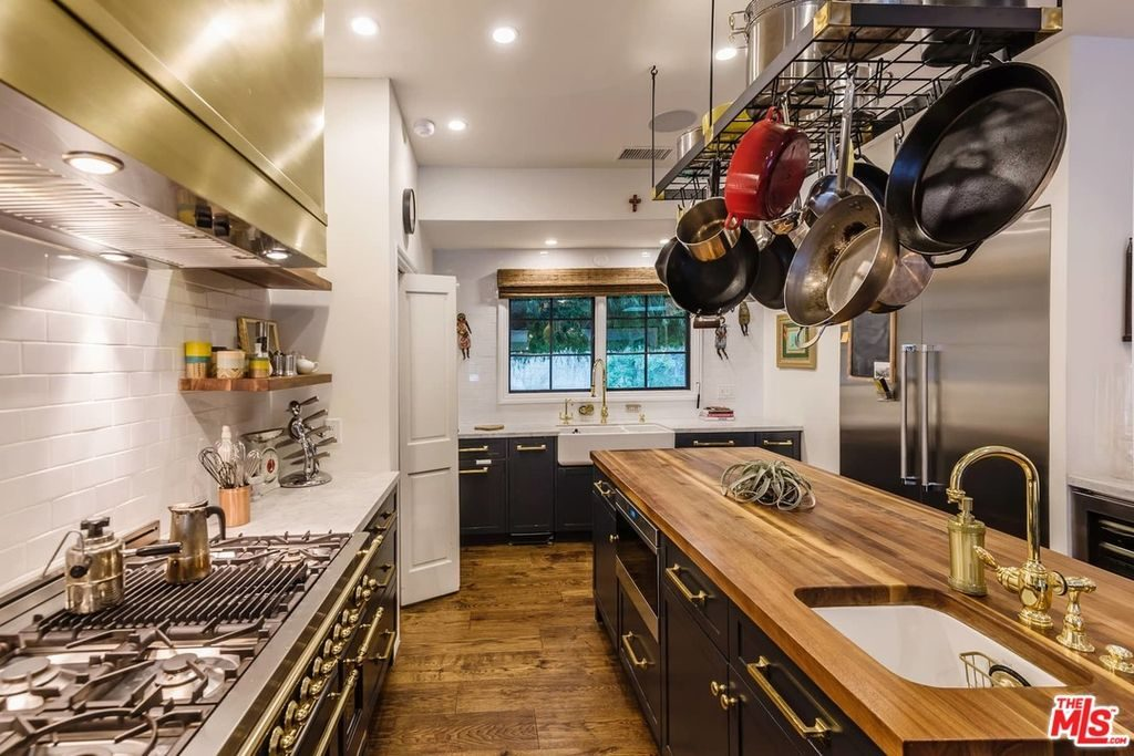 A metal pot rack is suspended over a wooden top island that's fitted with an undermount sink and brass fixtures. It is surrounded by stainless steel appliances and gray cabinets against the white subway tile backsplash.