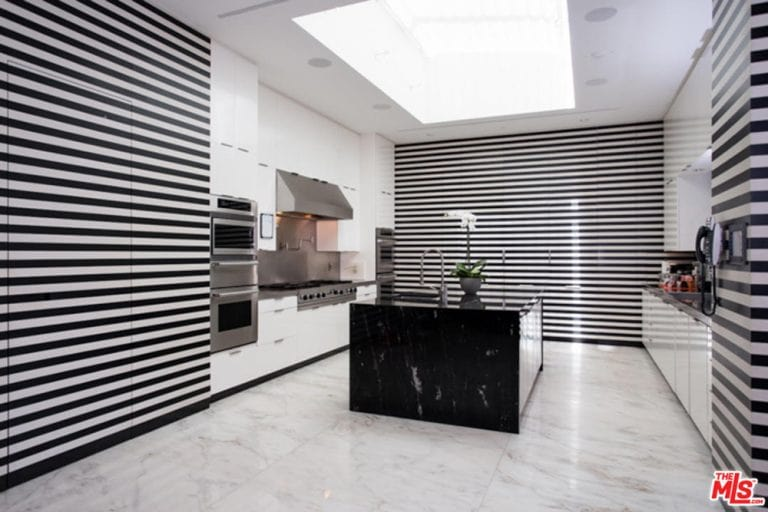 Black and white striped walls create statement in this kitchen with marble tiled flooring and a regular white ceiling fitted with a skylight. It is equipped with stainless steel appliances and an undermount sink on a black center island.