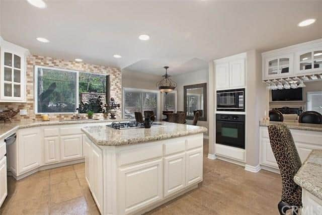 Beige subway tile backsplash sets a striking backdrop to the glazed window and glass front cabinets. This kitchen offers black appliances and a central island topped with granite countertop and a built-in cooktop.