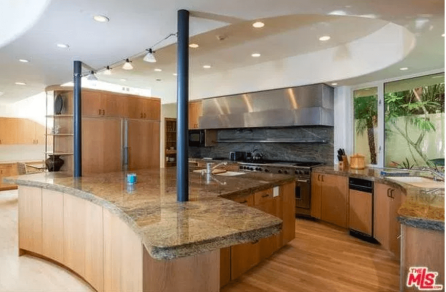 Black columns support the granite top island with an undermount sink and built-in storage. It is accompanied by inset appliances and wooden cabinets under the bay window.