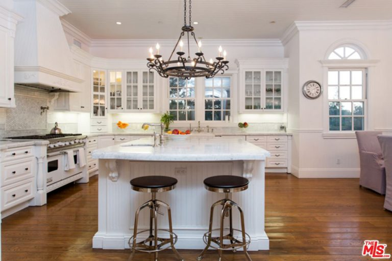 This kitchen boasts white appliances and cabinetry along with a beadboard island that's paired with round bar stools. It is lighted by a wrought iron chandelier and recessed ceiling lights.