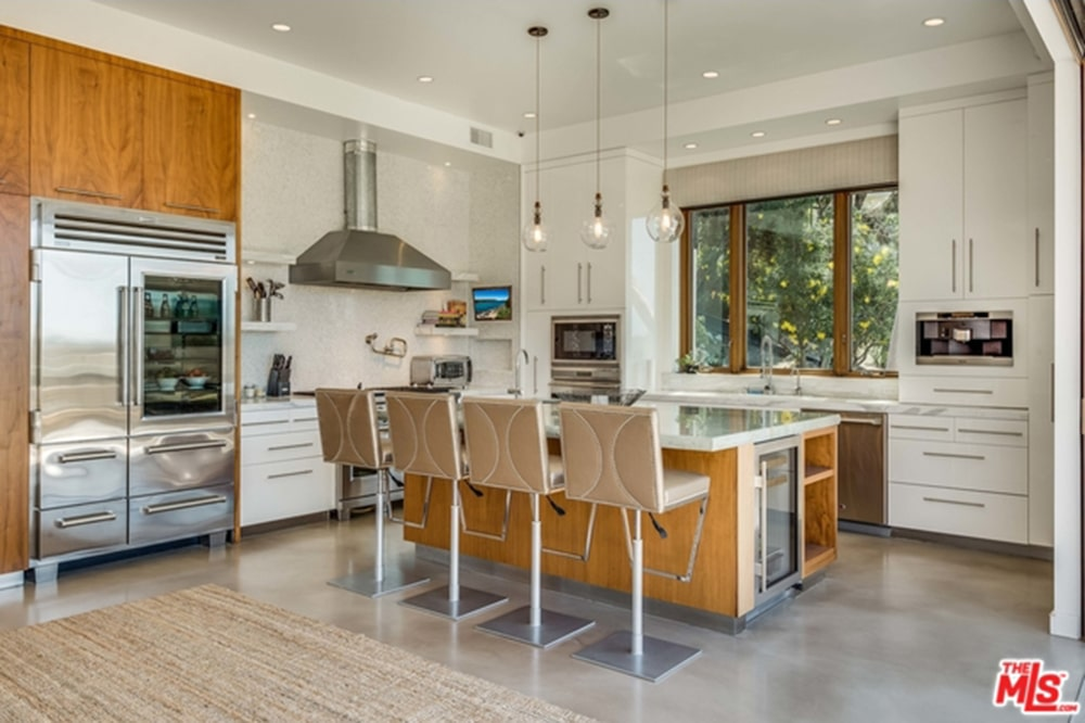 Sleek cushioned stools sit at a wooden breakfast island that's fitted with built-in shelves and a wine fridge. It is accompanied by stainless steel appliances and white cabinetry along with a jute rug that lays on the concrete flooring.
