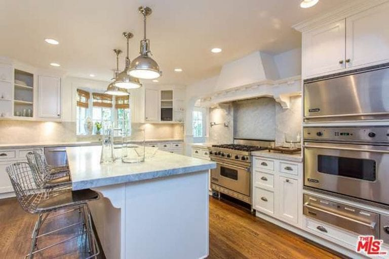 White kitchen with rich hardwood flooring and a bay window covered in wicker roman shades. It includes inset appliances and a marble top island lined with chrome dome pendants and perforated counter chairs.