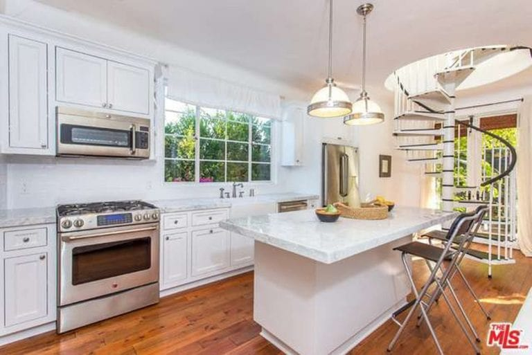 White cabinetry fades into the white walls in this kitchen with inset appliances and a marble island situated next to the winding staircase. It is complemented by glass dome pendants and metal counter chairs over the wide plank flooring.