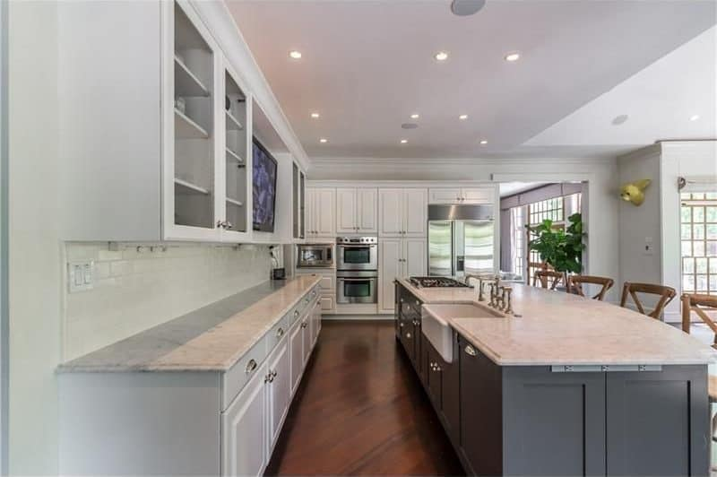 A gray marble top island with farmhouse sink and wooden counter chairs provide a sleek contrast to the white and glass front cabinetry within the kitchen. It has dark hardwood flooring and a regular white ceiling mounted with recessed lights.