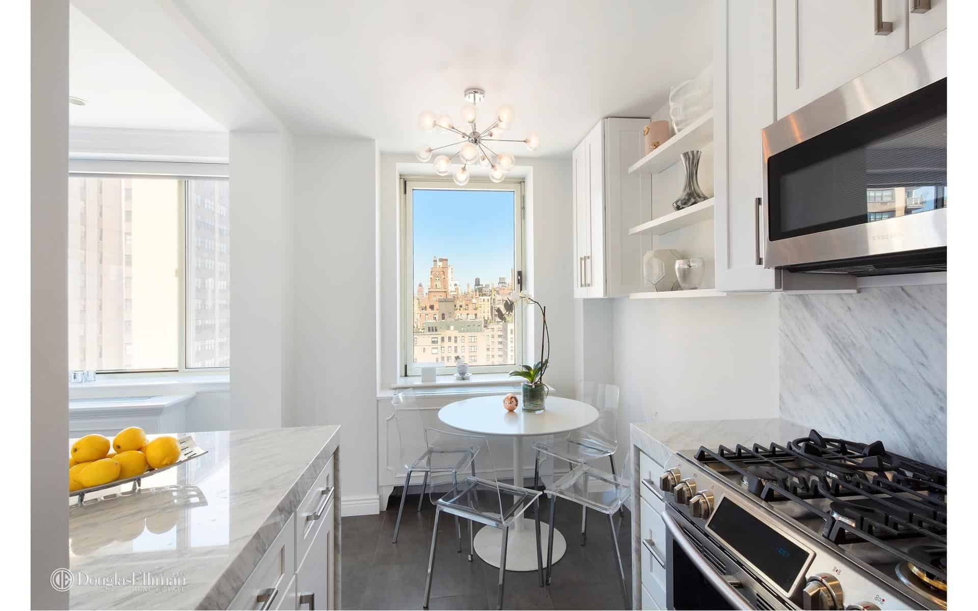 An eat-in kitchen features white cabinets and a marble backsplash that matches the countertops. It is completed with a round dining table and glass chairs by the picture window framing an incredible city view.
