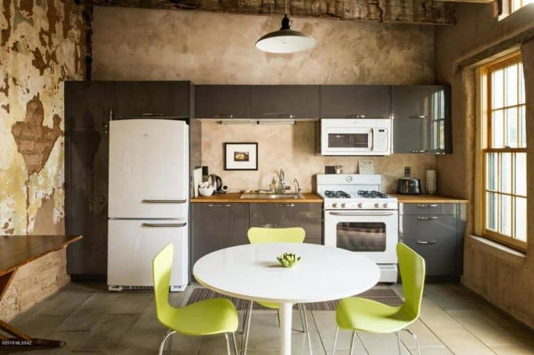 Rustic kitchen with a round dining set and white appliances contrasted by gray cabinets in a high gloss finish. It is illuminated by a dome pendant light that hung from the wood beam ceiling.