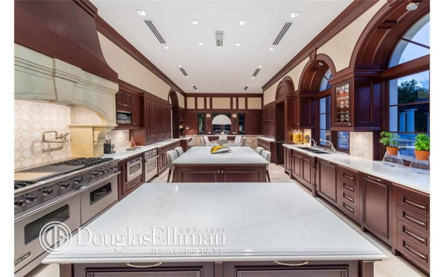 Dark wood cabinetry surrounds the marble top islands in this immense kitchen with arched windows and a regular white ceiling fitted with vents and recessed lights.