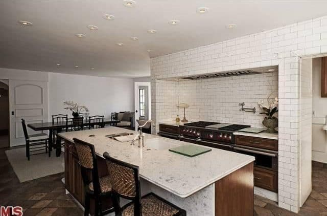A pair of wicker counter chairs sit at a marble top island that's fitted with an undermount sink and a chrome faucet. It is complemented by wooden cabinets and range fixed against the brick tiled wall.