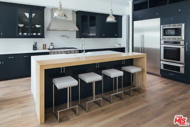Chrome dome pendants illuminate the white island with a light wood eating counter lined with sleek bar stools. It is surrounded by stainless steel appliances and dark gray cabinets against the white walls.
