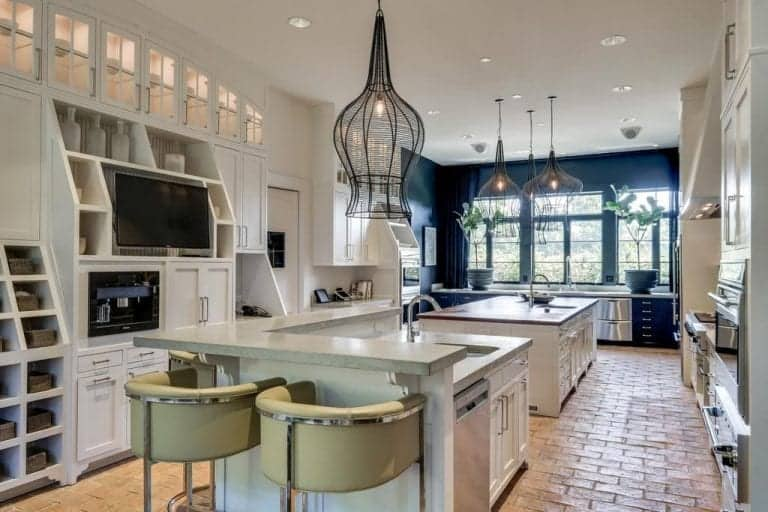 Stainless steel appliances and along with white cabinets run throughout this kitchen that's illuminated by stylish pendant lights. It showcases a flat-screen display and two islands over brick flooring.