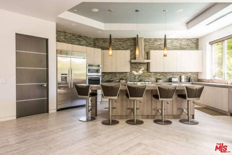 Unique bar stools sit at a natural wood island that's lighted by warm pendants hanging from a tray ceiling. It is accompanied by matching cabinetry and inset appliances against the linear mosaic tile backsplash.