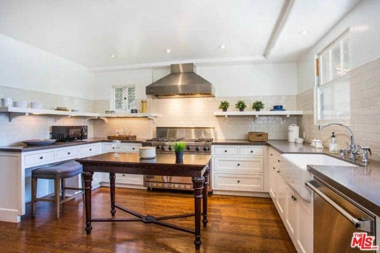 A leather cushioned seat complements the white cabinets that are topped with gray countertops and a farmhouse sink. It is accompanied by stainless steel appliances and a dark wood table in the middle that sits on a polished hardwood flooring.