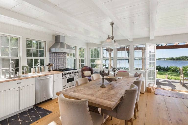Airy kitchen with a stunning beachfront view features white beadboard cabinets and a wooden dining set lit by glass dome pendants that hung from the beamed ceiling. It is completed with stainless steel appliances and a black patterned rug over the wide plank flooring.