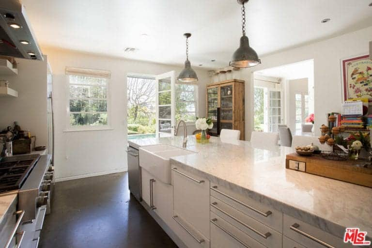 Galley kitchen with concrete flooring and a glazed door leading out to the backyard with a serene pool. It includes floating shelves and a marble top island fitted with a dual farmhouse sink and a gooseneck faucet.