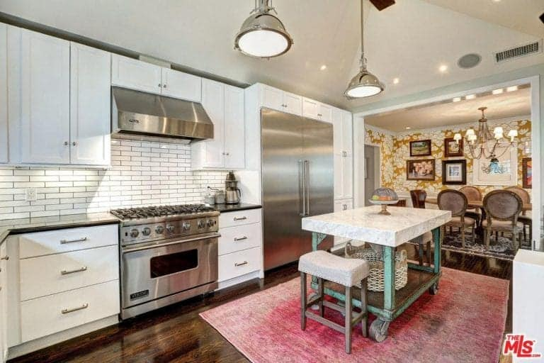 A red distressed rug over hardwood flooring stands out in this kitchen with a marble top island and white cabinets fixed against the subway tile backsplash. There's a dining space next to it that's decorated with an eclectic gallery.