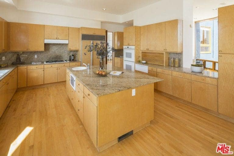 Cozy kitchen with wooden cabinetry and a matching granite top island that harmoniously blends in with the hardwood flooring for a cohesive look. It is equipped with an undermount sink and white appliances.