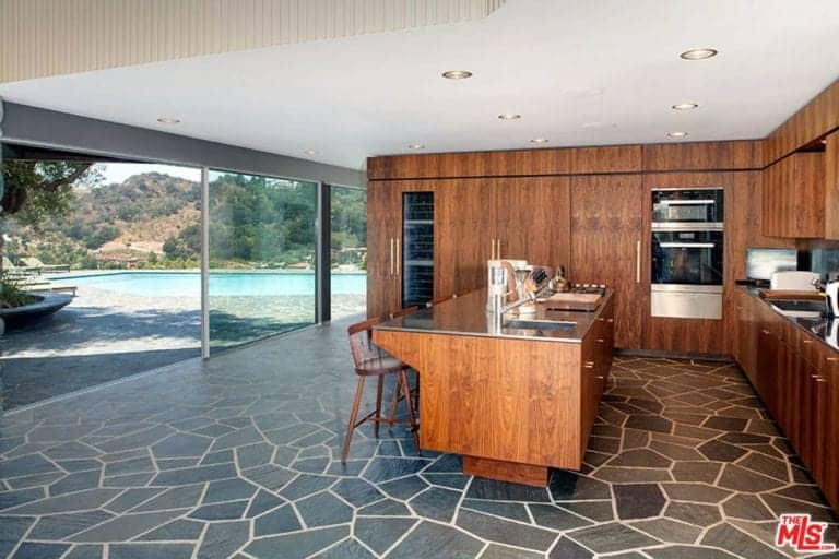 Cushioned round back stools sit at a wooden island matching with the cabinetry that's fitted with inset appliances. It has gorgeous flagstone flooring and a glass sliding door that opens to a sparkling pool with a breathtaking view.