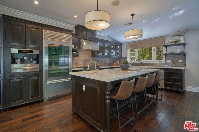 Cozy kitchen with dark wood cabinetry and a matching island with white marble countertop lined with leather bar chairs. It is illuminated by drum pendants and recessed ceiling lights.