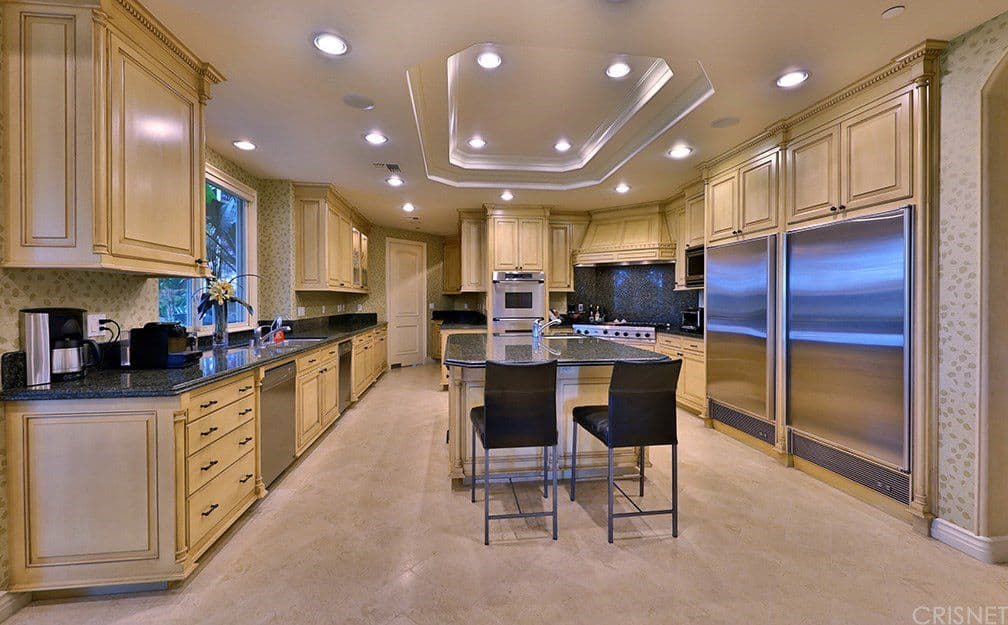 Clad in patterned wallpaper, this kitchen features beige cabinetry and a matching granite top island paired with black counter chairs. It is illuminated by recessed lights mounted on the tray ceiling.