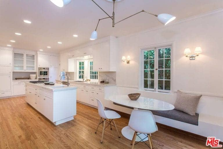 White cabinetry goes well with the hardwood flooring in this kitchen with stainless steel appliances and a breakfast nook illuminated by wall sconces and a contemporary chandelier.