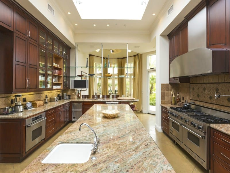This kitchen boasts glass floating shelves and wooden cabinetry along with a granite top island underneath a skylight. It is fitted with an undermount sink and a gooseneck faucet.