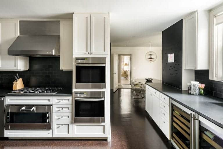 White cabinetry sets a striking contrast to the black subway tile backsplash and countertops in this kitchen with stainless steel appliances and built-in wine fridge.