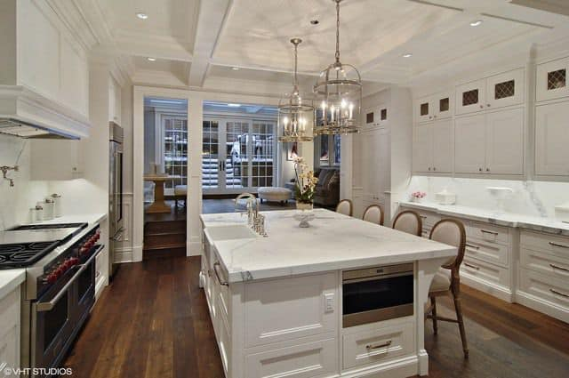 White kitchen illuminated by recessed lights and a pair of glass pendants that hung from the coffered ceiling. It has inset appliances and a marble top island complemented by beige round back chairs.