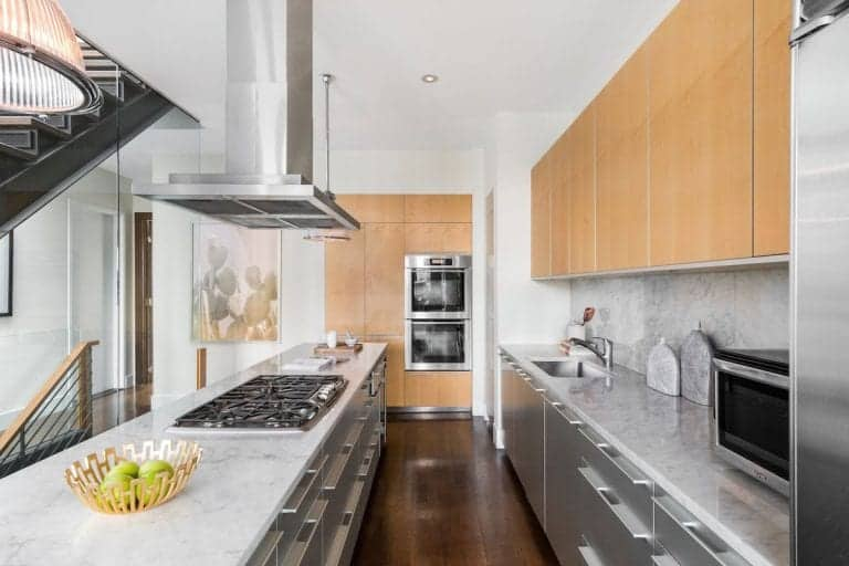 This kitchen offers wooden and stainless steel cabinets matching with the appliances and the central island under a sleek range hood. It is fitted with a built-in cooktop and a gray marble countertop.