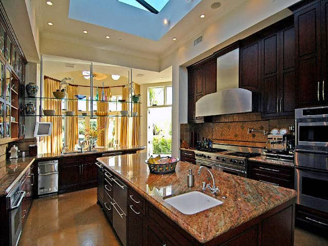 Floating glass shelves and dark wood cabinetry surround a matching island that's topped with an undermount sink and granite countertop. It has tiled flooring and a tray ceiling mounted with recessed lights and a large skylight.