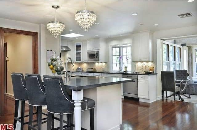 Gray upholstered chairs sit at a granite top island that's illuminated by crystal pendant lights. It is accompanied by stainless steel appliances and white cabinetry that blends in with the walls and ceiling.