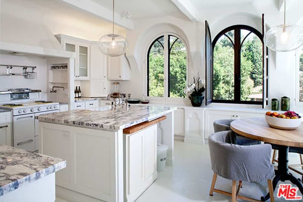 White eat-in kitchen with arched windows and beamed ceiling mounted with clear glass globe pendants. It includes white appliances and granite top countertops along with a wooding dining table surrounded by gray round back chairs.