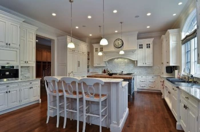 This kitchen boasts white cabinetry and a pair of center islands over the dark hardwood flooring. It is illuminated by glass dome pendants and recessed ceiling lights.