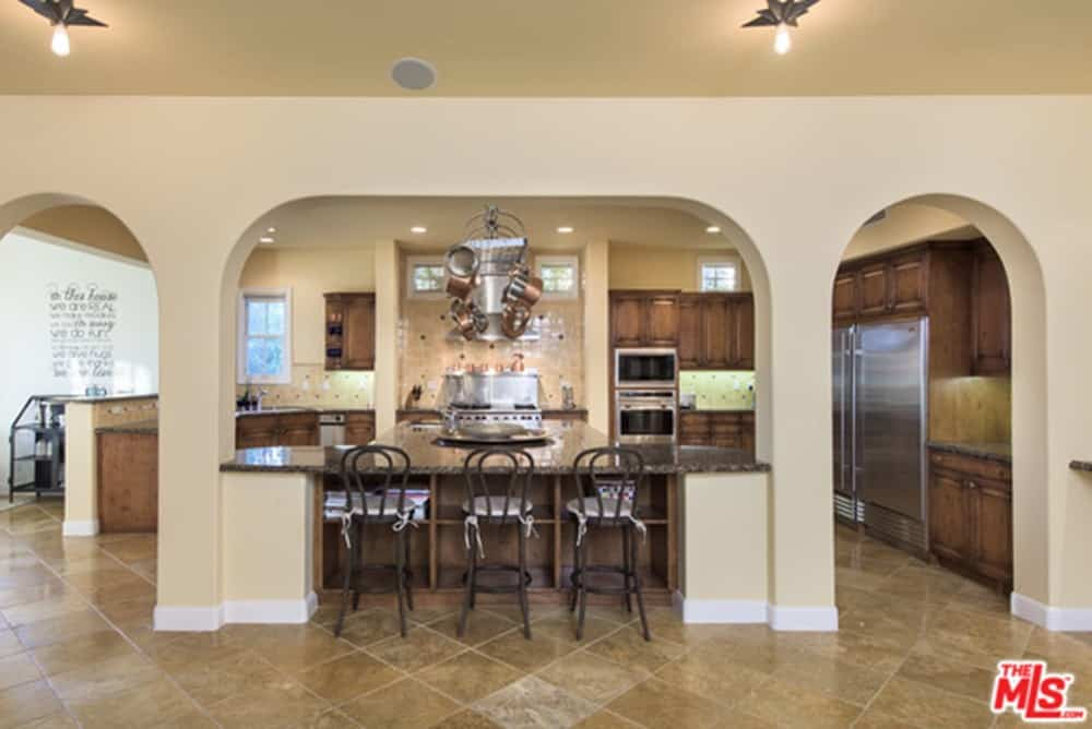 Mediterranean kitchen surrounded by open archways and granite top peninsulas along with dark wood cabinetry and stainless steel appliances. There's a chrome pot rack in the middle that's filled with copper pots.