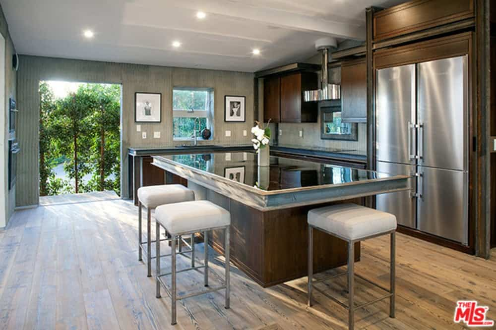 Wooden cabinetry surrounds the mirrored top island that's complemented by white cushioned stools over the natural hardwood flooring. A serene outdoor view can be seen through the large doorway of this kitchen.