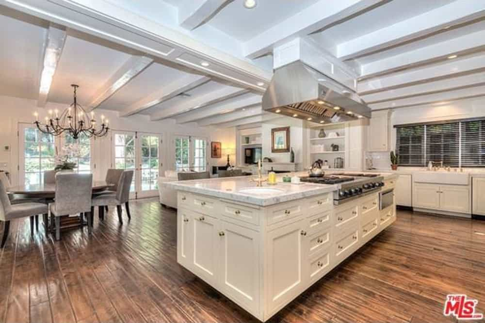An open concept kitchen offers white cabinetry and a matching center island with a marble countertop and a built-in cooktop. It is equipped with an undermount sink and stainless steel vent hood that's fixed on the beamed ceiling.