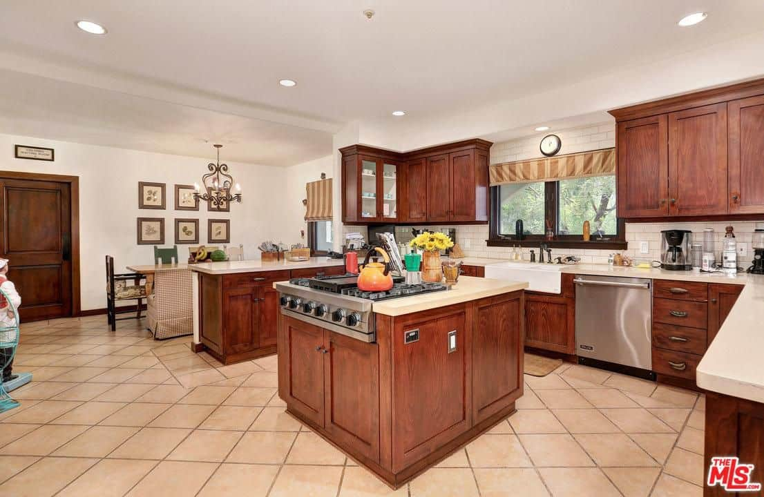 Gallery frames accentuate the eclectic dining set in this kitchen with wooden cabinetry and a matching island fitted with a built-in cooktop. It has beige tiled flooring and glazed windows dressed in striped roman shades.