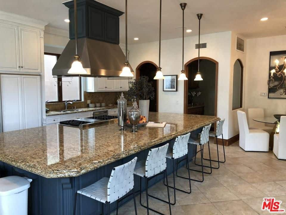 A stainless steel range hood is suspended over a grayish blue island that's topped with a granite countertop and a built-in cooktop. It is lined with glass dome pendants and woven bar chairs over beige tiled flooring.