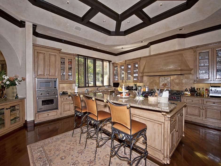 Ornate counter chairs on a floral rug complement the two-tier island with granite countertops and an undermount sink. This kitchen showcases rich hardwood flooring and a tray ceiling framed with black beams.