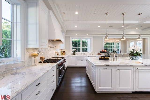 Light and airy kitchen features white cabinetry and a matching marble top island lighted by chrome dome pendants that hung from the shiplap ceiling. It includes stainless steel appliances and white framed windows contrasted by dark hardwood flooring.