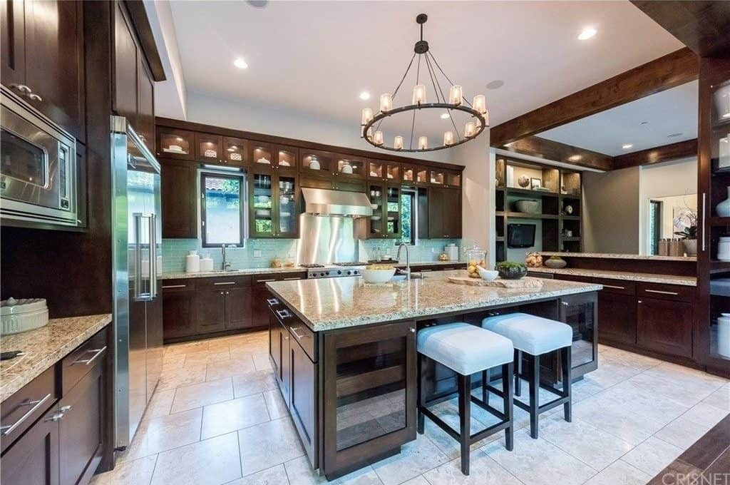 A round chandelier illuminates the granite top island that's fitted with an undermount sink and wine fridges. It is surrounded by stainless steel appliances and dark wood cabinetry over beige tiled flooring.