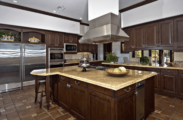 A stainless steel range hood is suspended over a granite top island that's fitted with ample storage and a built-in cooktop. It is surrounded by inset appliances and dark wood cabinetry against the herringbone backsplash.
