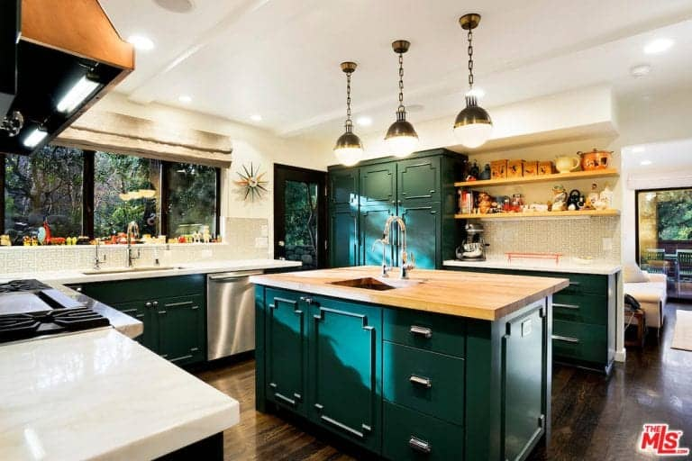 Green cabinetry and a matching central island add a sleek accent in this kitchen with wooden and marble countertops along with undermount sinks that are paired with gooseneck faucets.