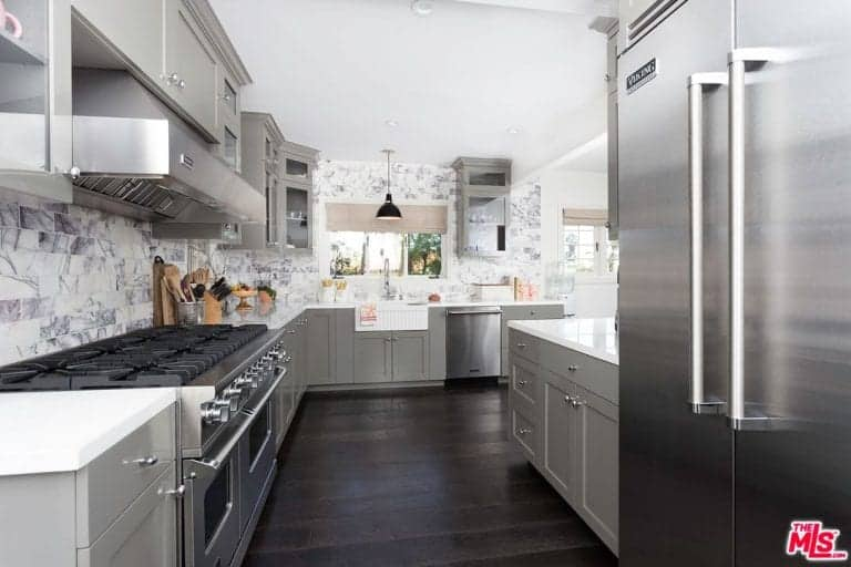 This kitchen features stainless steel appliances and gray cabinetry against the marble subway tile backsplash. It has dark hardwood flooring and a picture window covered in beige roller blinds.