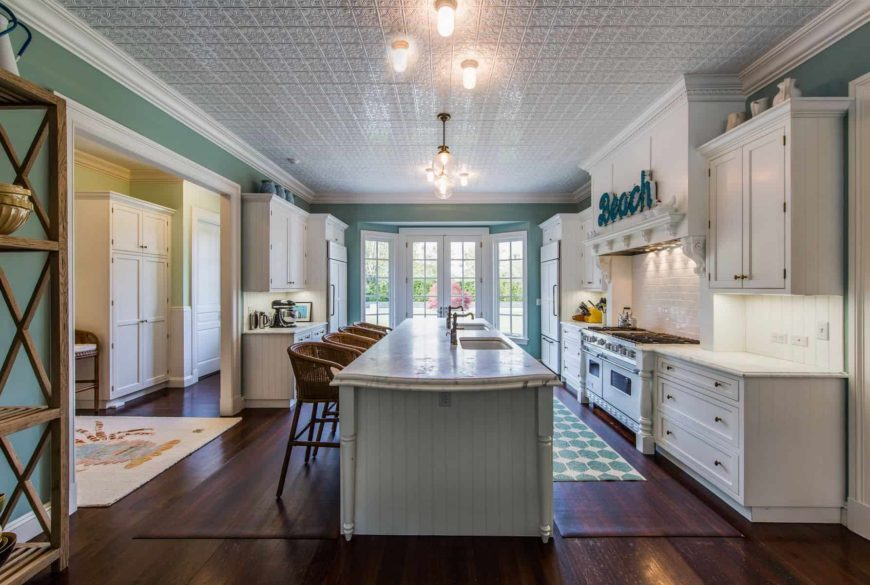 Beach style kitchen filled with white appliances and cabinetry along with a mint green beadboard island that's lined with wicker round back stools over dark hardwood flooring topped by various styled rugs. It has a white ornate ceiling and a French door leading out to the backyard.