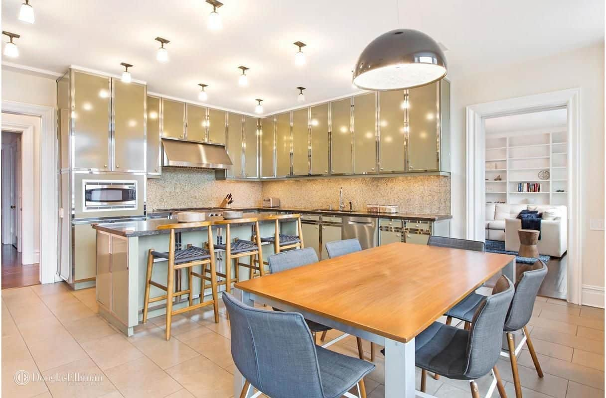 Eat-in kitchen showcases custom cabinetry with chrome accents along with a granite top island that's complemented by round back counter chairs. There's a cozy dining set on the side that's lighted by an oversized dome pendant.