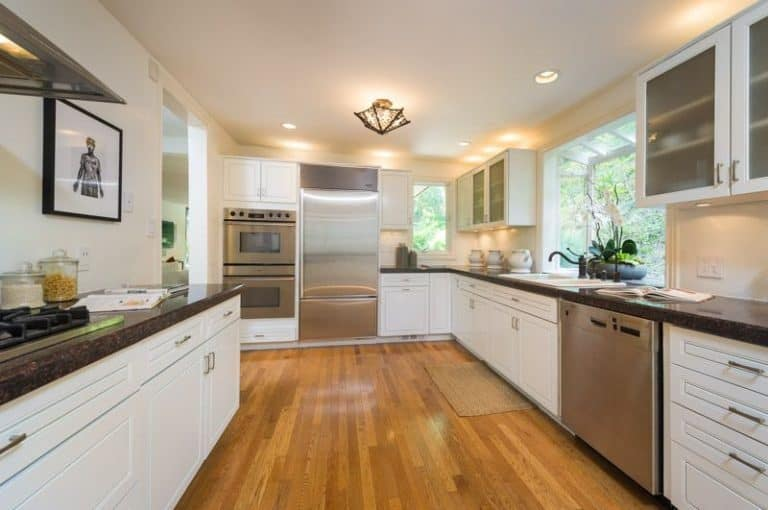 The bright kitchen boasts inset appliances and white cabinetry contrasted by black granite countertops. It is illuminated by a gorgeous semi-flush mount light and recessed ceiling lights.